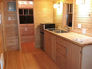 The California Cabin features a spacious kitchen area with flat cook top, sink and refrigerator. Some tiny house people choose to add a dishwasher, or laundry machines. There are many options available.